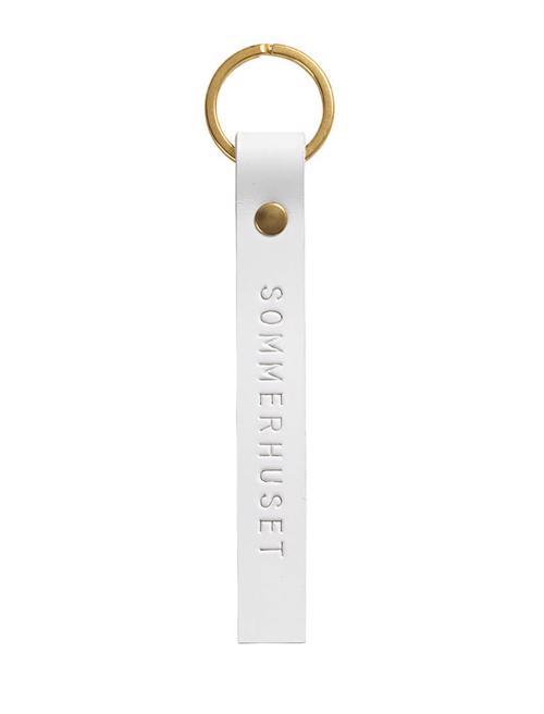 Key ring <br /> White dyed leather, brass details and nature print